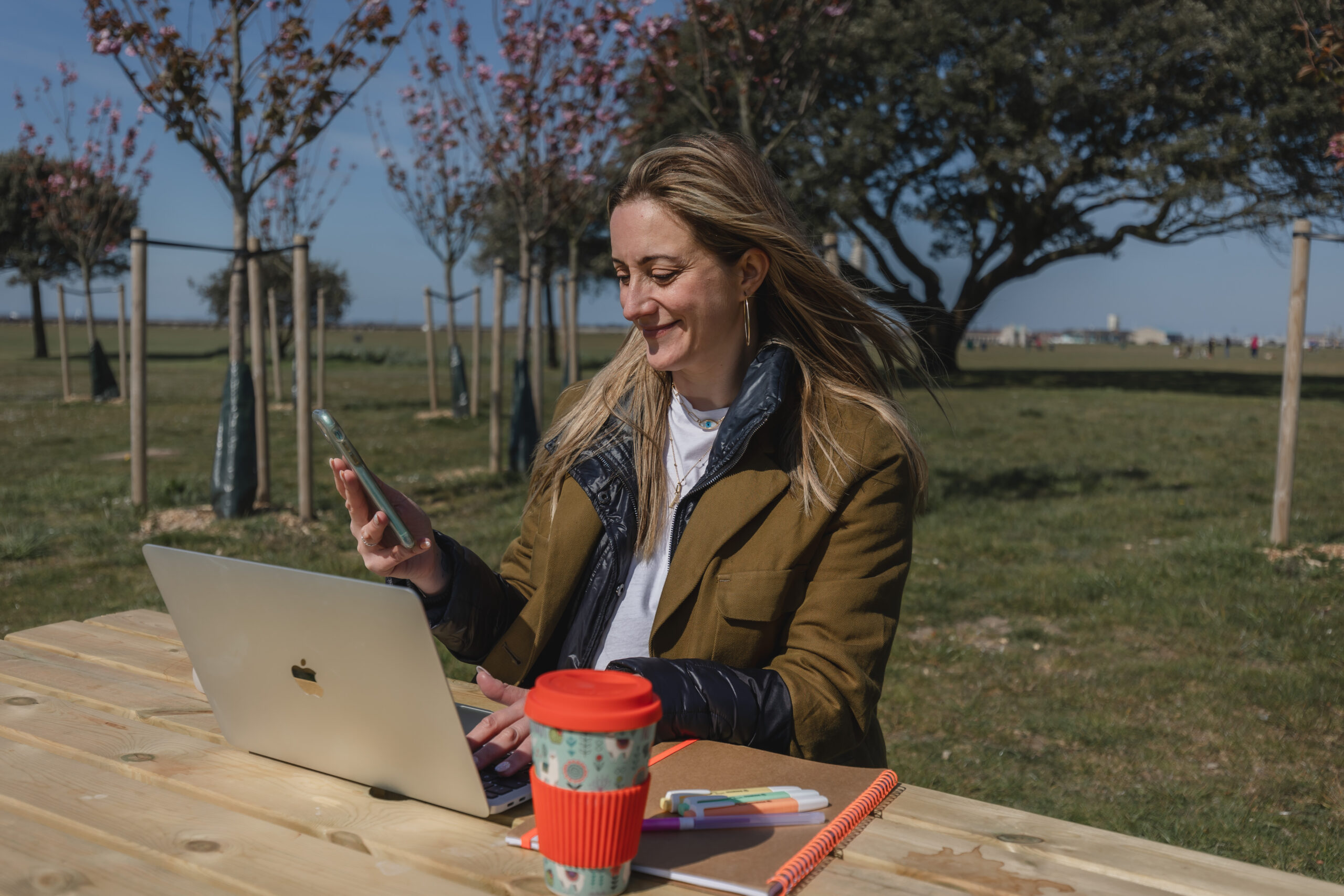 Alanna Smith is looking at her mobile phone. Her laptop is in front of her as well as a coffee cup and a notepad. She is outside sat at a wooden picnic bench.